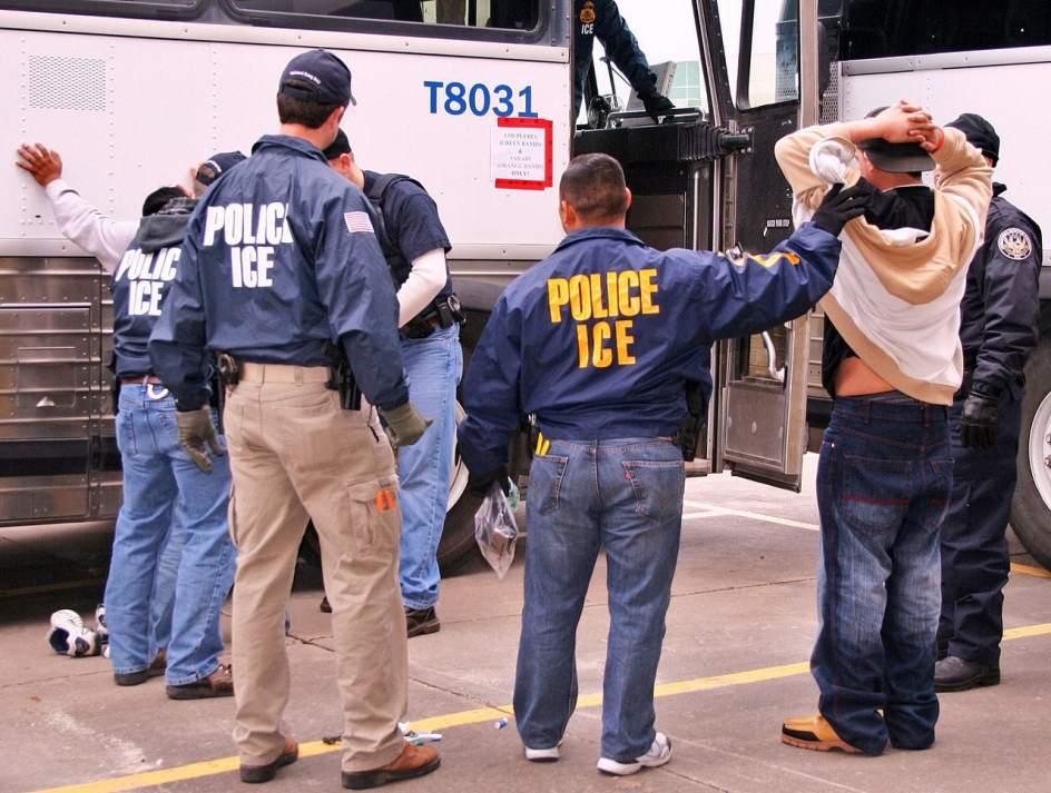 Un grupo de indocumentados es registrado por varios agentes de ICE antes de subirlos al transporte que los conducirá a un centro de detención de Estados Unidos. Foto: Tomada de internet.