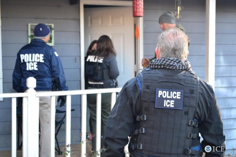 Agentes de ICE interrogan a una persona en la puerta de su casa. La Fuerza de Deportación del gobierno de Trump continúa sus operativos. Foto: Tomada de internet.