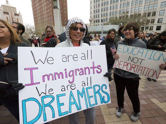 Un grupo de jóvenes beneficiarios de DACA conocidos como Dreamers sostienen junto a otros inmigrantes varios carteles en defensa del programa durante una manifestación. Foto: Tomada de internet.