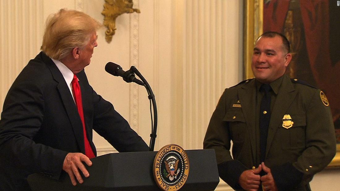El presidente de Estados Unidos, Donald Trump (izq.), invita al agente de la Patrulla Fronteriza, Adrián Anzaldúa, a hablar ante el micrófono durante la ceremonia de homenaje a ICE y al CBP en la Casa Blanca el lunes 20 de agosto. Foto: Tomada de internet.