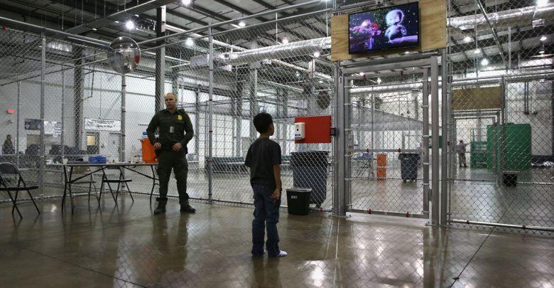 Un menor migrante recluido en un centro de detención de ICE mira la televisión ante la vigilancia de un guardia del lugar. Foto: Tomada de internet.