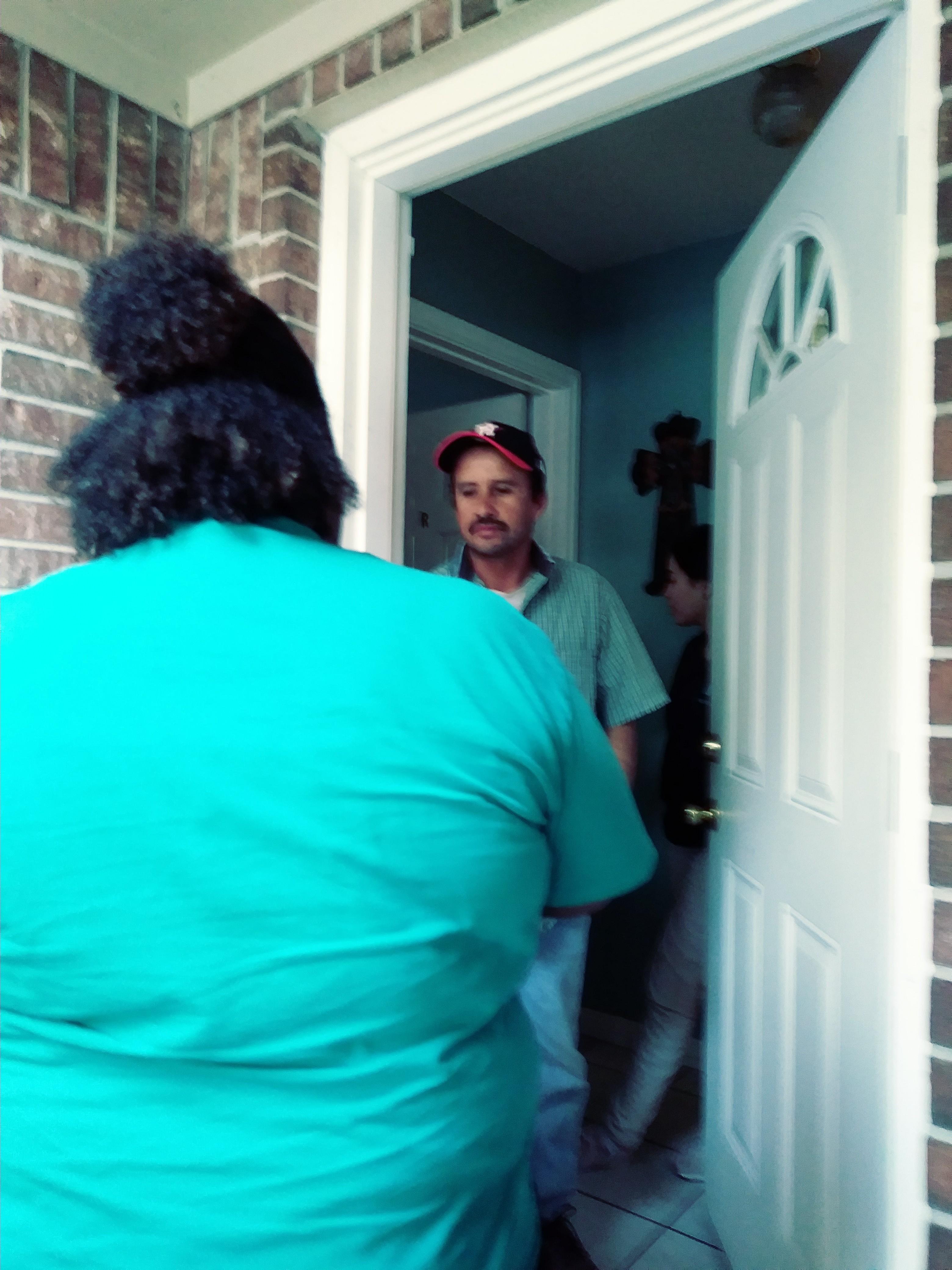 Almeisha Whitlock (de espaldas) da información electoral a Ricardo Cárdenas en la puerta de su domicilio en Houston, Texas. Foto: David Torres/America's Voice