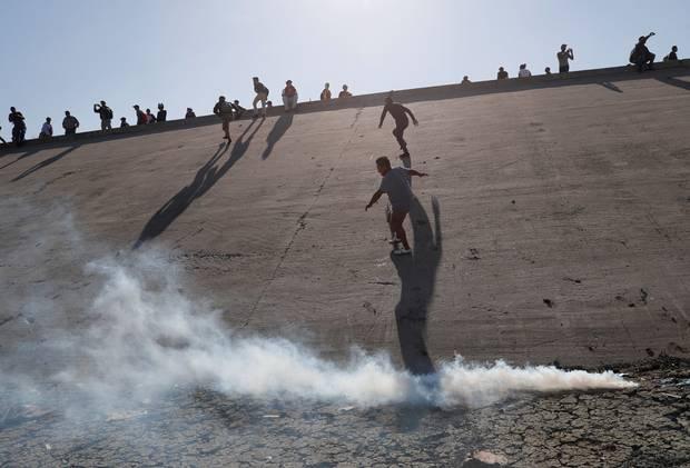 Migrantes corren despavoridos luego de que agentes fronterizos de Estados Unidos les arrojaran gas lacrimógeno, tras de que intentaran cruzar la frontera sur en la zona de California en busca de asilo. Foto: Tomada de internet.