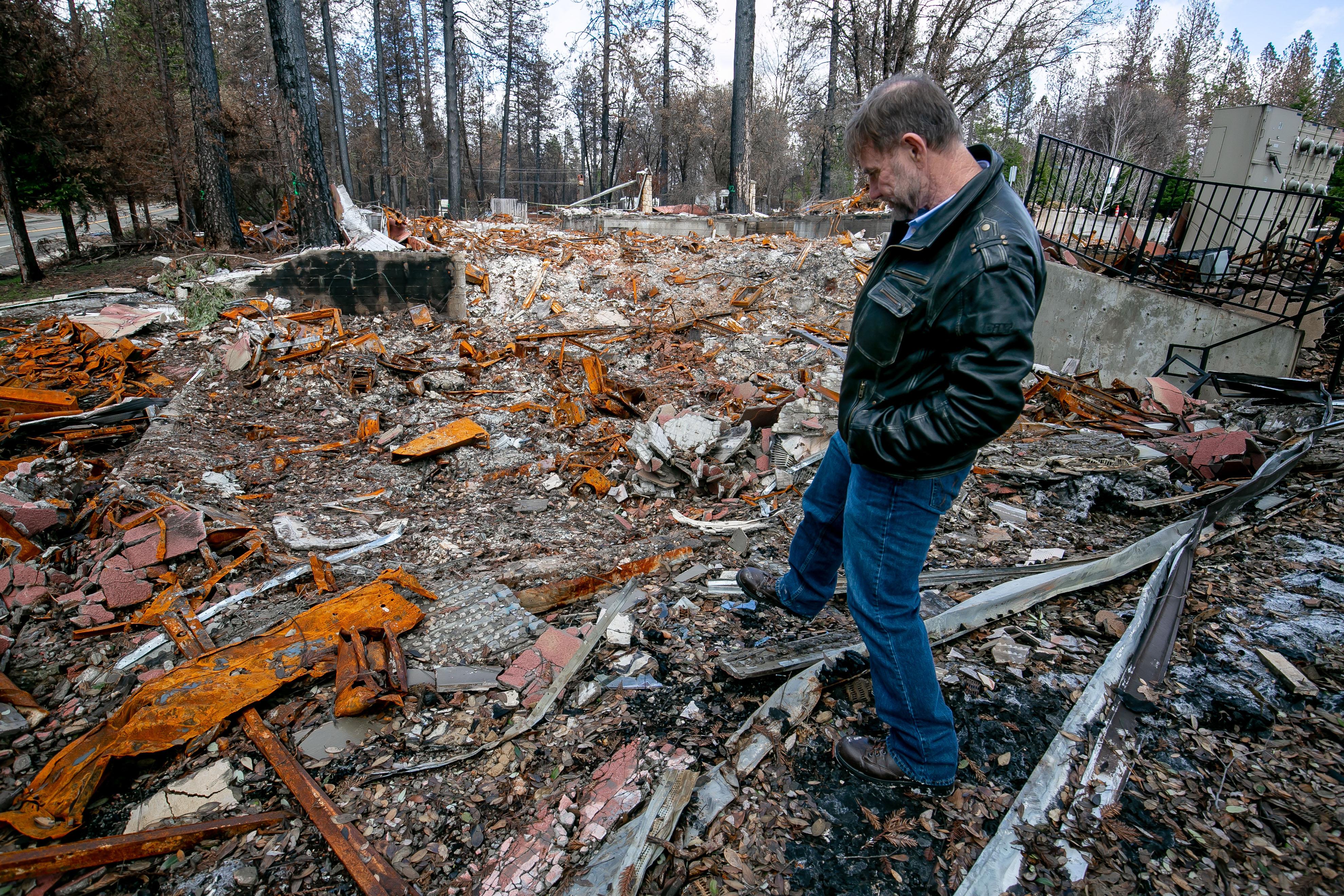 Walt Taber, de Paradise Medical Group camina sobre los escombros de lo que fue su oficina.