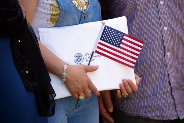 """Una persona sostiene una bandera y un sobre con sus documentos tras su ceremonia de naturalización en Estados Unidos. Con su nueva regla de """"carga pública"""", el gobierno dificultará la regularización de millones de migrantes. Foto: Tomada de internet."""