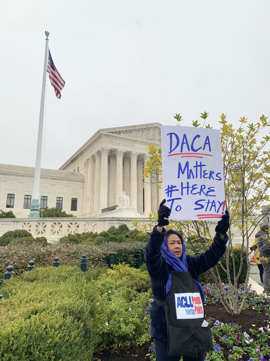 Una joven activista sostiene un cartel en apoyo a DACA, donde dice que el programa es importante, junto a la etiqueta que indica que los Dreamers están en el país para quedarse. Foto: Tomada de internet.