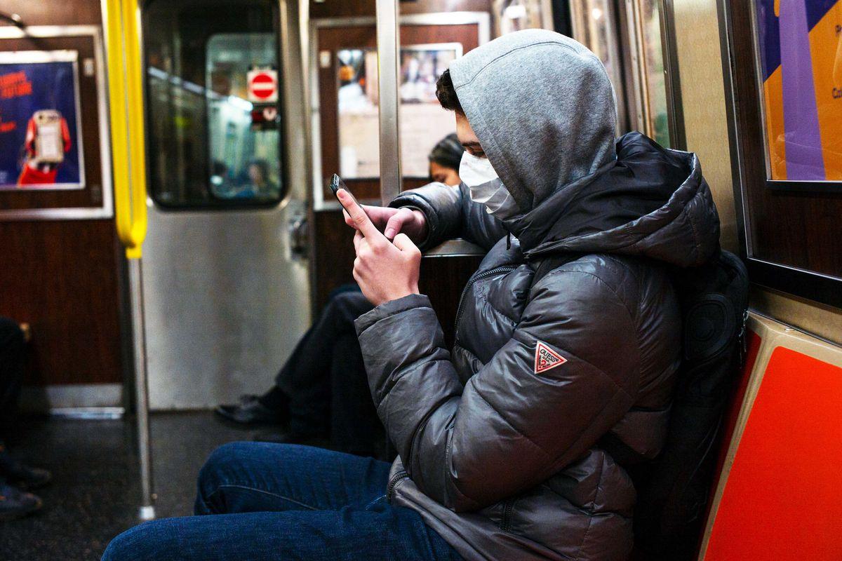 Un pasajero con mascarilla protectora revisa su teléfono mientras viaja en transporte público. Cada vez se ve menos gente en trenes y autobuses en EEUU debido a las medidas de asilamiento para evitar contagio de coronavirus. Foto: Tomada de internet.